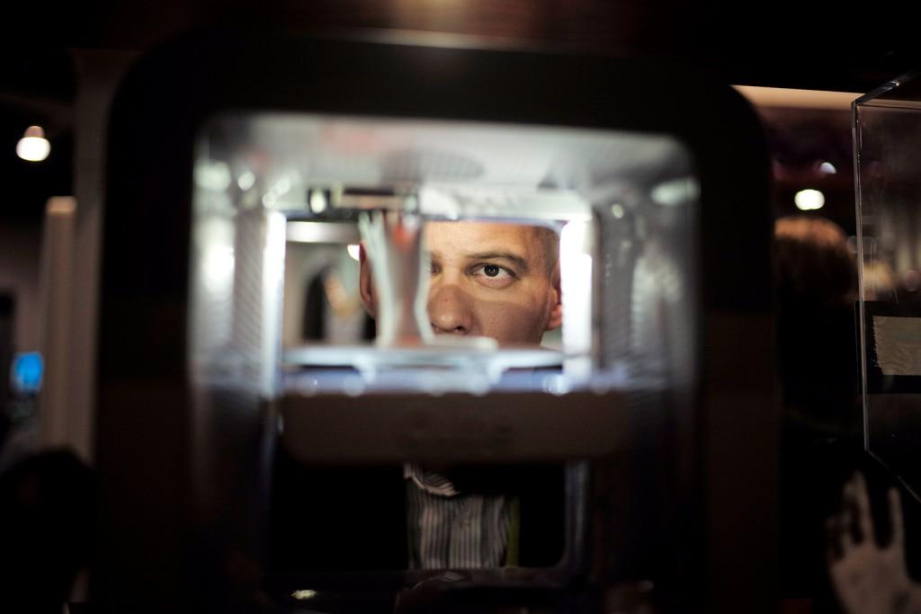 Ian Schick relojes una mano de plástico que se está imprimiendo en una impresora 3D en el stand de 3D Systems en el CES Internacional, 7 de enero de 2015, en Las Vegas.  Jae C. Hong / AP